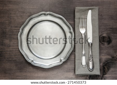 Antique silver cutlery and vintage tin plate on old wooden background - stock photo