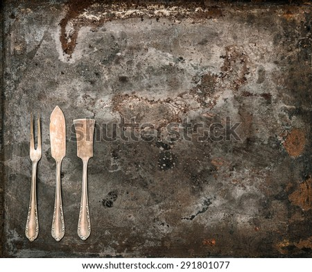 Antique silver cutlery on rustic metal background. Old tableware. Vintage style toned picture - stock photo