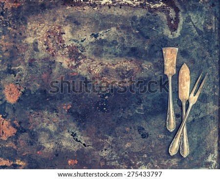 Antique silver cutlery on rustic textured metal background. Old tableware. Vintage style toned picture - stock photo