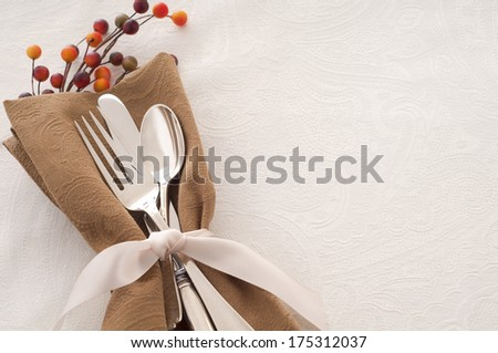 Antique Silverware Place Setting in a Brown Napkin and Tied with Ribbon on White Background, a Table Cloth with space or Room for text, Copy, words - stock photo