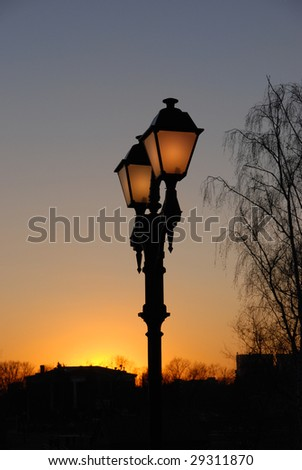 Antique street lamp in a park at sunset - stock photo
