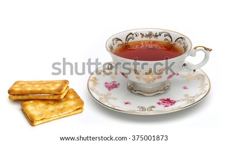 Antique tea cup with biscuits on white background - stock photo