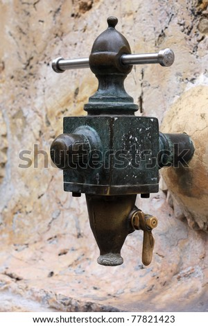 Antique the water tap in the Spanish city. - stock photo