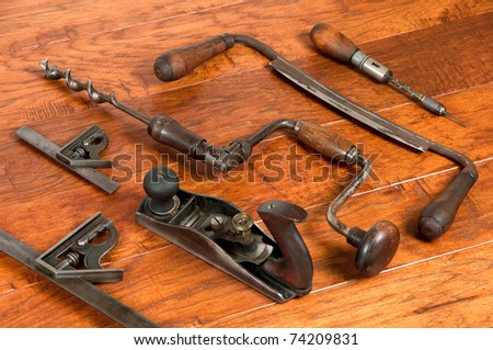 Antique tool arrangement including plane, draw knife, punch drill, slide squares in two sizes, and bit brace on wooden background. All tools were well used in their day. - stock photo