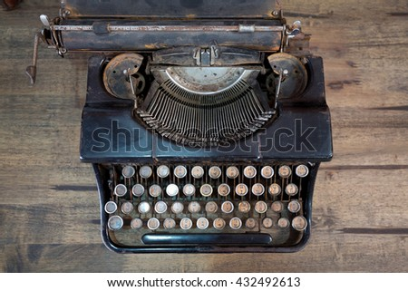 Antique typewriter in vintage and grunge looks on a wooden table. - stock photo