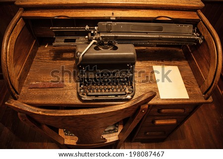 Antique typewriter on an old wooden desk - stock photo