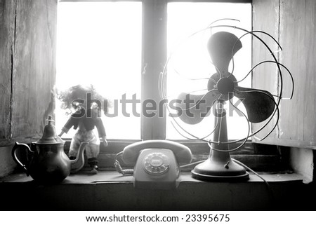 Antique vintage air fan, doll and phone at the window back-light - stock photo