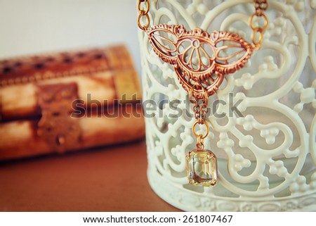 antique vintage necklace on wooden table. retro filtered image.  selective focus  - stock photo