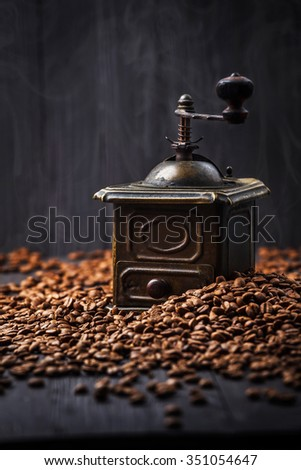 Antique vintage retro bronze coffee mill on black wooden board with roasted coffee beans - stock photo