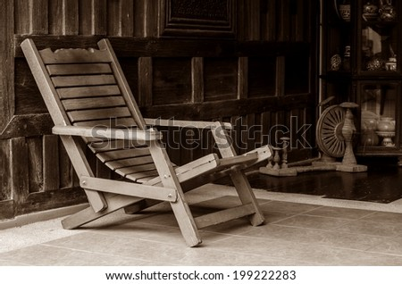 Antique wooden arm chair in old wooden house. - stock photo