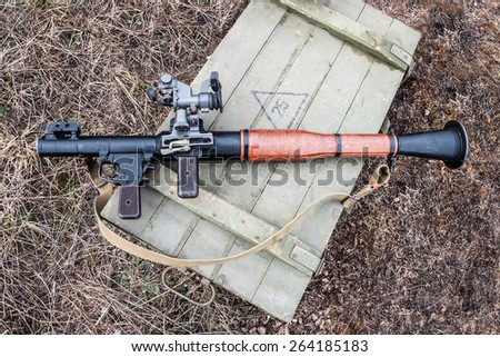 antitank grenade launcher lying on a crate of ammunition - stock photo
