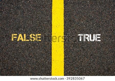 Antonym concept of FALSE versus TRUE written over tarmac, road marking yellow paint separating line between words - stock photo