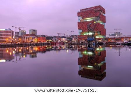 ANTWERP, BELGIUM - APRIL 4: Museum aan de Stroom (MAS) caught the purple glow of sunset in Antwerp, Beligum on April 4th, 2014. The museum is a recent addition to Antwerp's skyline, opening in 2011. - stock photo