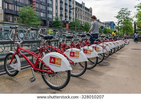ANTWERP, BELGIUM - AUG 11: Man is parking a bicycle at an automatic bicycle rental for shared bicycles on August 11, 2015 in Antwerp, Belgium - stock photo