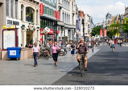 ANTWERP, BELGIUM - AUG 11: People and cyclists in the main shopping street of Antwerp downtown in the city on August 11, 2015 in Antwerp, Belgium - stock photo