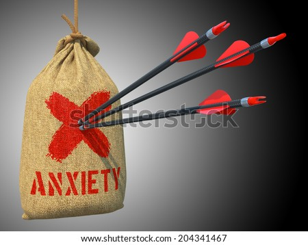 Anxiety - Three Arrows Hit in Red Mark Target on a Hanging Sack on Grey Background. - stock photo