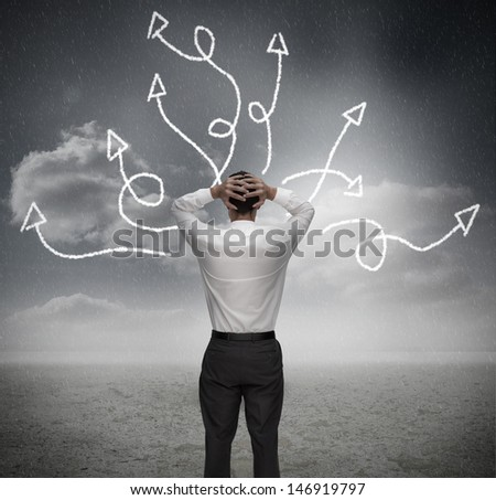 Anxious businessman looking at jumbled arrows with hands on head - stock photo