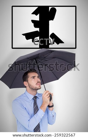 Anxious businessman sheltering with umbrella against cctv - stock photo