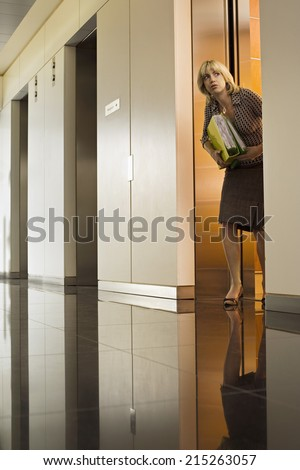 Anxious businesswoman exiting office elevator, looking nervously down corridor, surface level - stock photo