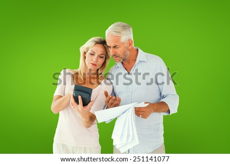 Anxious couple working out their bills against green vignette - stock photo