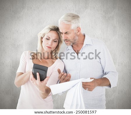Anxious couple working out their bills against weathered surface - stock photo