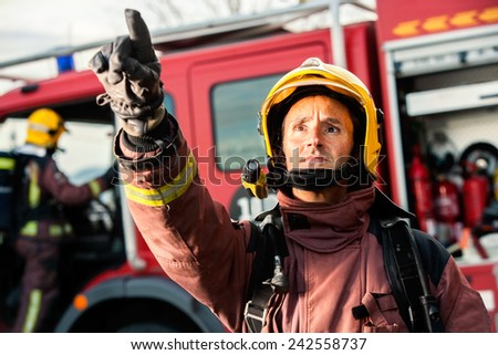 Anxious fireman with fire truck in background pointing at danger situation. - stock photo