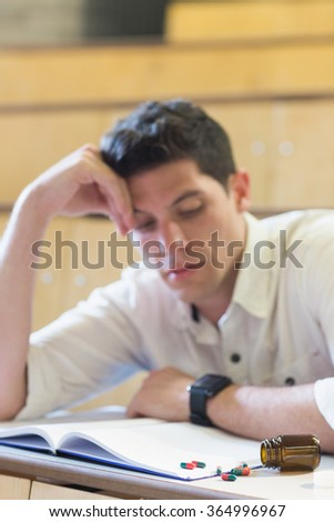 Anxious male student during exam in lecture hall - stock photo