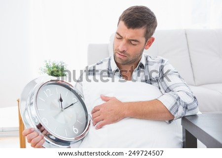 Anxious man beside clock with a pillow at home in the living room - stock photo
