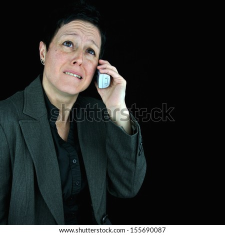 Anxious, nervous businesswoman in suit, biting her lip and looking upwards in despair whilst making/taking a difficult phone call. Black background with copy space. - stock photo