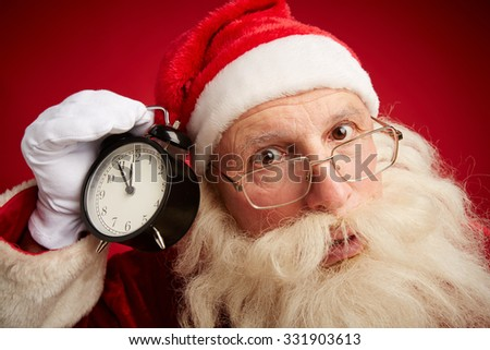 Anxious Santa with alarm clock showing five minutes to xmas - stock photo