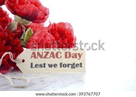ANZAC Day, April 25, greeting with Lest We Forget and bunch of red silk poppies on white marble table, with copy space.  - stock photo
