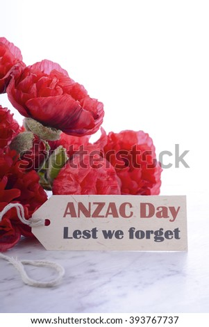 ANZAC Day, April 25, greeting with Lest We Forget and bunch of red silk poppies on white marble table.  - stock photo