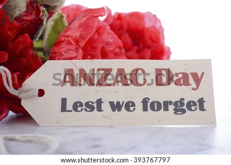 ANZAC Day, April 25, greeting with Lest We Forget and bunch of red silk poppies on white marble table, closeup.  - stock photo