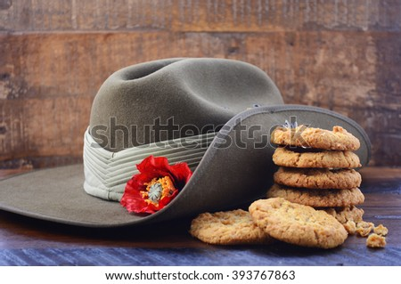 Anzac Day Australian Army slouch hat with stack of traditional Anzac biscuits on dark vintage wood background, with copy space. - stock photo
