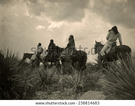 Apaches. Before the storm- Four Apache on horseback on horseback under storm clouds. photo by Edward S. Curtis, 1906 - stock photo