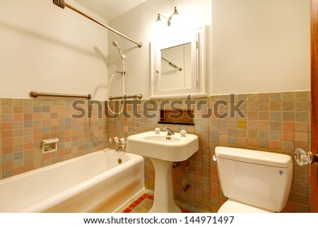 Apartment Bathroom with old antique fixtures and white tub. - stock photo