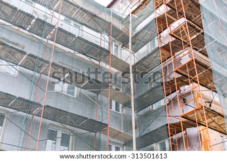 apartment building exterior under renovation with scaffolding and green netting - stock photo