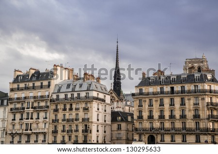 Apartment buildings and steeple, Paris - stock photo