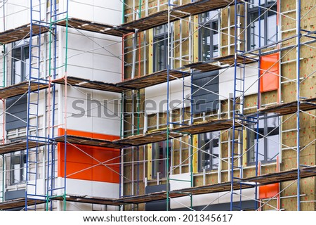 Apartment construction in the process of being built with scaffolding - stock photo