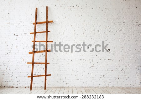 Apartment Renovation. Wooden Ladder near white Brick Wall in empty Room - stock photo