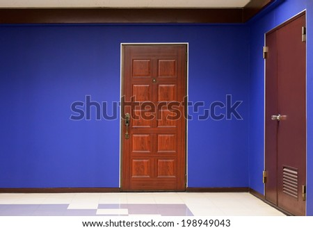 Apartment wooden door and blue wall background texture - stock photo