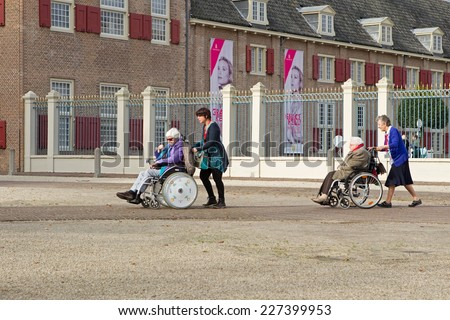 Apeldoorn, Netherlands - October 31, 2014: wheelchair with companions left the entrance to Het Loo Palace in Apeldoorn.  - stock photo