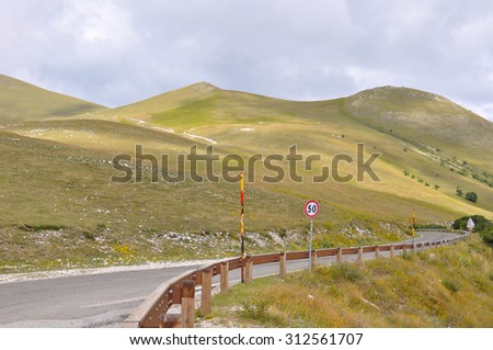 Apennines landscapes, meadows, cloudy sky and road signs of Castelluccio, Umbria,Italy - stock photo