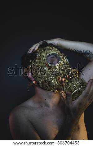 apocalypse, depression and danger man with golden gas mask - stock photo