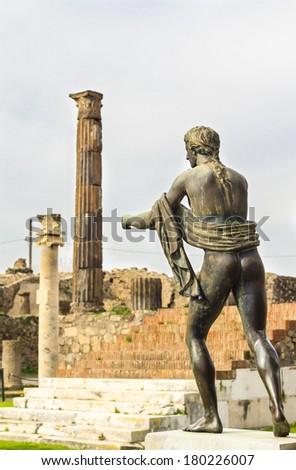 Apollo statue in the ruins of Pompeii (apollo temple), Italy. The Temple of Apollo was built in the third centruy B.C. and ruined during Vesuvius eruption in 79AD - stock photo