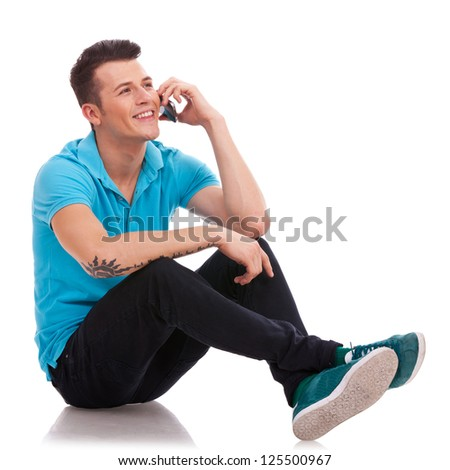 Appealing young casual man speaking on the phone and sitting with his legs crossed. He is looking somewhere up and smiling - stock photo
