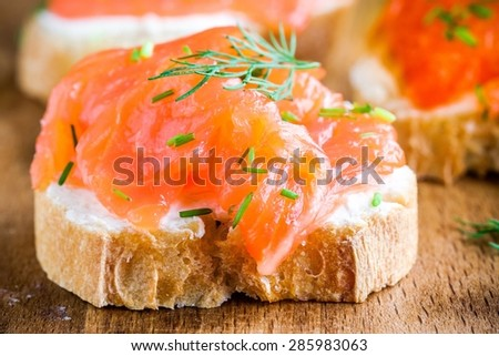 Appetizer canape of baguette with smoked salmon, cream cheese closeup - stock photo