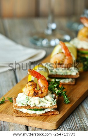 Appetizer canape with shrimp and cucumber on plate on table close up - stock photo