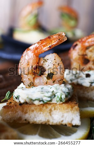 Appetizer canape with shrimp and lemon on plate on table close up - stock photo