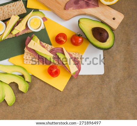 Appetizer. Crispbread with beef ham, cheese, avocado, eggs - stock photo